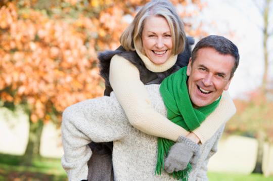 Senior man giving woman piggyback ride